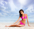 A young brunette woman on a beach background and attractive caucasian laying in pink swimsuit the image is taken with sand sky Stock Photo