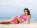 A young brunette woman on a beach background and attractive caucasian laying in pink swimsuit the image is taken with sand sky Royalty Free Stock Images