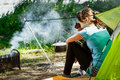 Young brunette woman in blue blouse sitting in a forest near the tent.tourist resting on a halt near a fire with smoke. Royalty Free Stock Photo