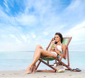 A young brunette woman drinking a cocktail and relaxing on the beach attractive caucasian in white swimsuit image is taken Stock Image