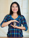 Young brunette woman facing camera, holding glass jar with coins inside, smiling happily Royalty Free Stock Photo