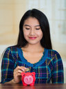 Young brunette woman facing camera, holding piggy bank and placing money inside it, smiling happily Royalty Free Stock Photo