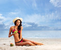 A young brunette woman in a hat eating fresh grapes healthy beautiful and sexy white and red swimsuit the image is taken on the Stock Image