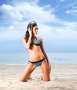 A young brunette woman with headphones on the beach and attractive caucasian in blue swimsuit listening to music in image is taken Stock Images
