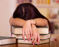 Young brunette woman lying bent over stack of books, appears to be asleep, tired student concept Royalty Free Stock Photo