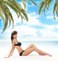 A young brunette woman on a sea resort background and attractive caucasian laying in black swimsuit the image is taken Royalty Free Stock Images