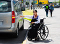 Young brunette woman sitting in wheelchair smiling with positive attitude, holding out arm looking for taxi, outdoors