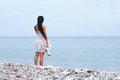 A young brunette woman standing near the sea Royalty Free Stock Images