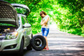 Young brunette woman stands near a silver car on the roadside with a broken wheel Royalty Free Stock Photo