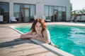 Young brunette woman in a swimming pool in blue swimming suit. Royalty Free Stock Photo