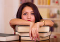 Young brunette woman wearing pink top lying bent over stack of books, tired facial expression and body language, student Royalty Free Stock Photo