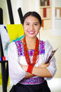 Young brunette woman wearing traditional andean clothing, holding paint brushes and posing, canvas behind, inside studio Royalty Free Stock Photo