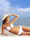 A young brunette woman in a white swimsuit on the beach Royalty Free Stock Images
