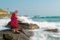 A young Buddhist monk stands on a rock in the ocean. Sri Lanka