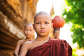 Young buddhist monks walking morning alms in old bagan myanmar Stock Photo