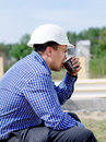 Young builder taking his coffee break engineer or architect sipping from a plastic mug as team continue working on site in the Royalty Free Stock Photos