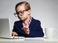 stock image of  Young business boy. funny child in glasses. little boss in office