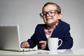 Young business boy. smiling child in glasses. little boss in office