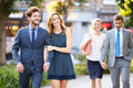Young business couples walking through city park together holding hands smiling Stock Image