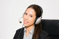 Young business dressed female working as telemarketer sitting in chair Stock Image