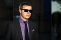 Young business man against office building in sunglasses Royalty Free Stock Images