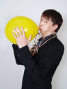 Young business man blowing up a yellow balloon Royalty Free Stock Photography