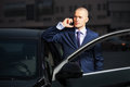 Young businessman calling on cell phone by car Royalty Free Stock Photo