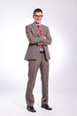 Young business man with hands crossed full length picture of a standing his and smiling for the camera on a gray background Stock Photography
