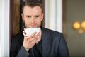 Young business man holding coffee cup at cafe portrait of Royalty Free Stock Photography