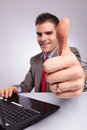 Young business man at laptop shows thumb up Royalty Free Stock Photo