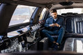 Young business man in limo typing on smart phone Royalty Free Stock Photo