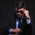 Young business man looks over his sunglasses taking off and looking into the camera them on black background Stock Image