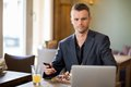 Young business man with mobilephone and laptop in portrait of confident businessman sitting coffeeshop Stock Photography