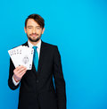 Young business man showing playing cards poker face on blue Stock Photos