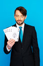 Young business man showing playing cards poker face on blue Royalty Free Stock Image