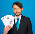 Young business man showing playing cards poker face on blue Stock Photo