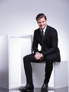 Young business man smiling for the camera while sitting handsome on a white cube Stock Photography