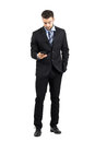 Young business man in suit reading message on his cellphone full body length portrait isolated over white studio background Royalty Free Stock Images
