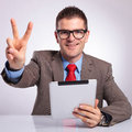 Young business man with tablet shows victory sign sitting at the desk a in his hand and showing the while smiling for the camera Royalty Free Stock Image