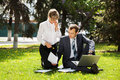 Young business people with laptop in a city park