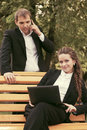 Young business people with laptop in city park