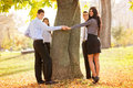 Young business people saving the nature group of standing in a park hugging a tree trunk with a smile on their faces looking at Stock Photos