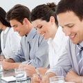 Young business people taking notes at a conference Royalty Free Stock Photos