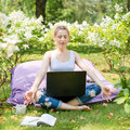 Young business woman doing yoga outside office building sitting in lotus position in the park with her laptop and cup of tea or co