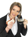 Young business woman eating a bacon sandwich and black coffee dslr royalty free image of attractive with dark hair holding cup of Royalty Free Stock Photos