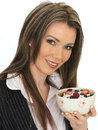 Young business woman eating a bowl of cereals with yogurt and be dslr royalty free image an attractive blond hair holding Stock Image