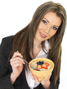 Young business woman eating a bowl of porridge with fresh fruit dslr royalty free image an attractive dark blonde hair blow and Stock Image