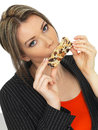 Young business woman eating a breakfast cereal bar dslr royalty free image of an attractive with dark blonde hair looking Royalty Free Stock Image