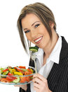Young business woman eating a fresh mixed salad dslr royalty feee image of attractive with dark blonde hair holding glass bowl Royalty Free Stock Photos