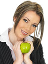 Young business woman eating a fresh ripe juicy green apple dlsr royalty free image of attractive holding cradling with both hands Stock Photography